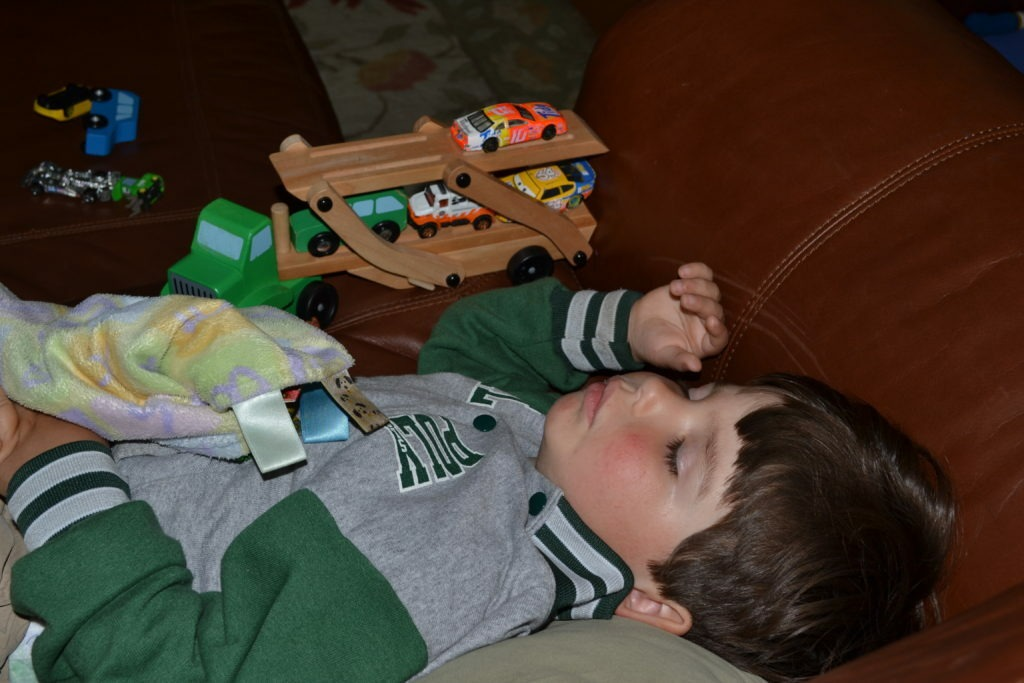 napping with his cars and trucks